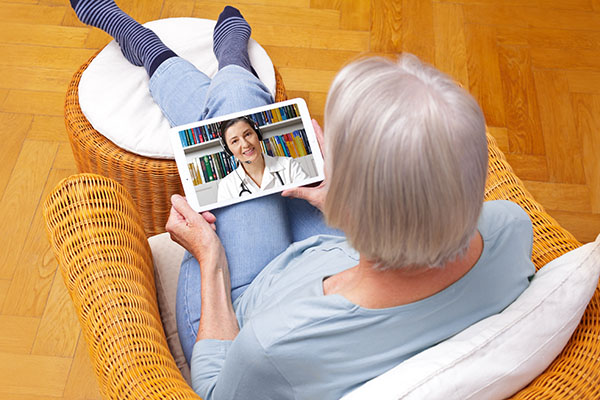 woman with tablet pc during an online consultation with her doctor in her living room